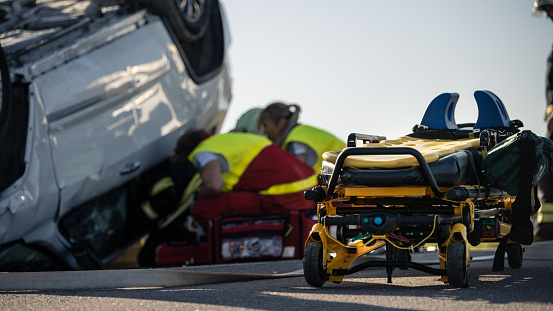 Paramedics and firefighters rescue an injured crash victim
