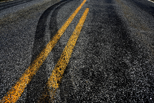 Close up of tire marks in a road, crossing over the double yellow lines